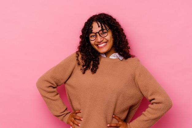 ピンクの背景に分離された若い混血の女性は、腰に手を保つことに自信を持っています。 Premium写真