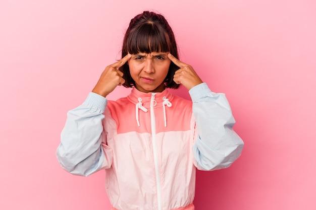ピンクの背景に分離された若い混血の女性は、人差し指を頭に向けたまま、タスクに焦点を当てました。