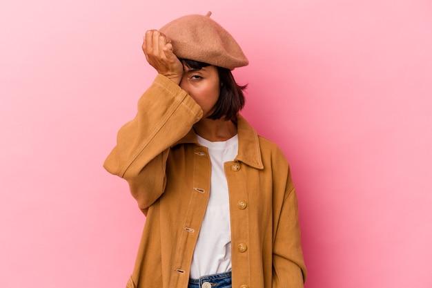 Молодая женщина смешанной расы изолирована на розовом фоне, забывая что-то, хлопая по лбу ладонью и закрывая глаза.