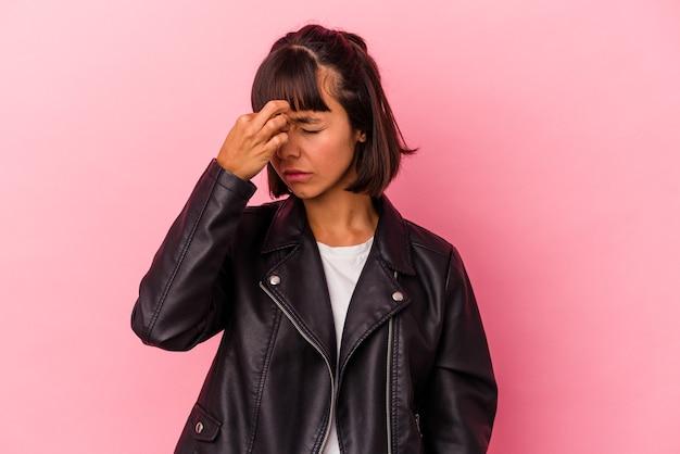顔の正面に触れて、頭痛を持っているピンクの背景に分離された若い混血の女性。