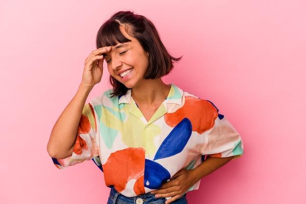 ピンクの背景に孤立した若い混血の女性は、たくさん笑ってうれしそうです。幸福の概念。
