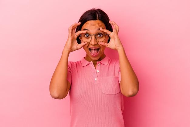 Молодая женщина смешанной расы изолирована на розовом фоне, держа глаза открытыми, чтобы найти возможность успеха.