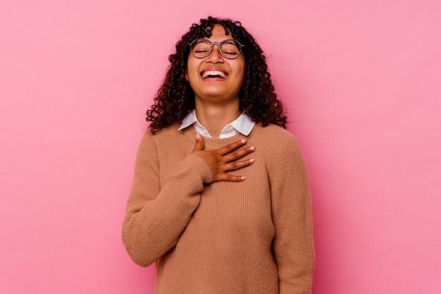 ピンクの背景に分離された若い混血の女性は、胸に手を置いて大声で笑います。 Premium写真