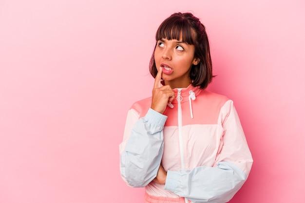 疑わしいと懐疑的な表情で横向きに見えるピンクの背景に分離された若い混血の女性。