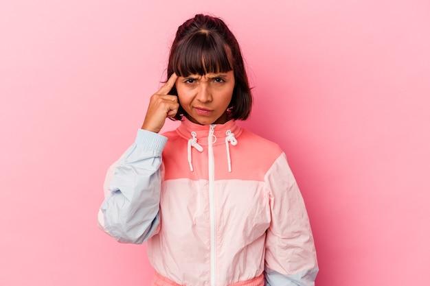 ピンクの背景に指で寺院を指して、考えて、タスクに焦点を当てて孤立した若い混血の女性。