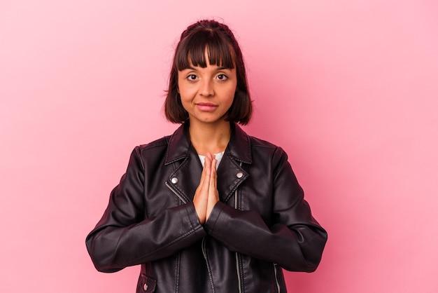 ピンクの背景の祈りで孤立した若い混血の女性、献身を示し、神のインスピレーションを探している宗教的な人。