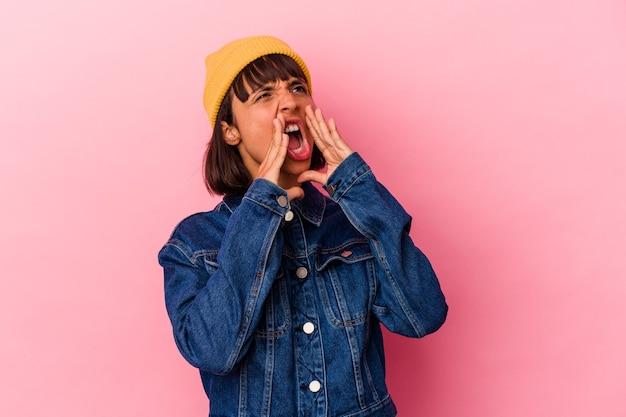 Молодая женщина смешанной расы, изолированные на розовом фоне крича, возбужденного вперед.