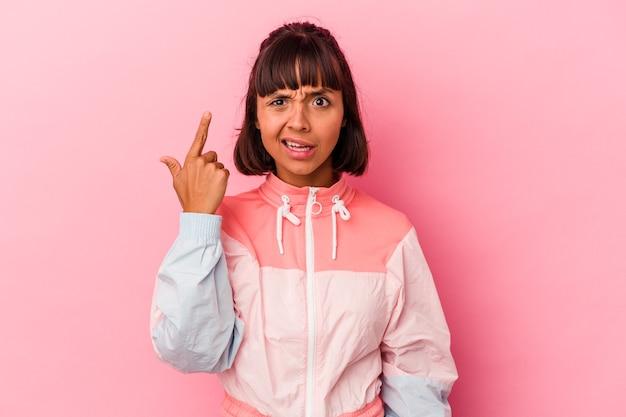 Молодая женщина смешанной расы изолирована на розовом фоне, показывая жест разочарования указательным пальцем.