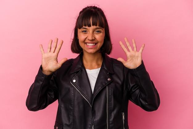 ピンクの背景に分離された若い混血の女性は、手で10番を示しています。