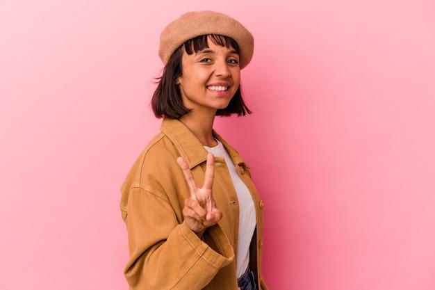 勝利のサインを示し、広く笑顔のピンクの背景に分離された若い混血の女性。