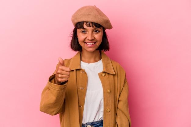 ピンクの背景に分離された若い混血の女性笑顔と親指を上げる