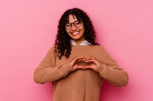 ピンクの背景に分離された若い混血の女性は、笑顔と手でハートの形を示しています。