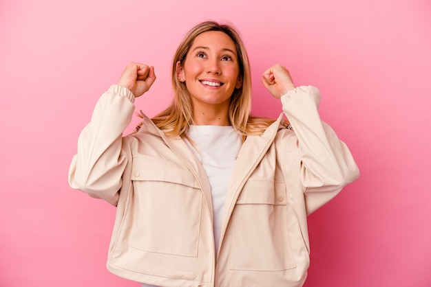 勝利、情熱と熱意、幸せな表現を祝うピンクで孤立した若い混血の女性。