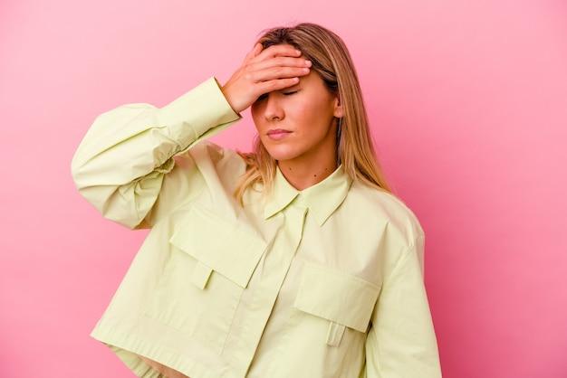 Молодая женщина смешанной расы изолирована на розовых трогательных висках и имеет головную боль.