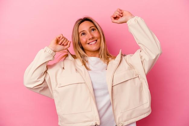 特別な日を祝うピンクの壁に孤立した若い混血の女性は、エネルギーでジャンプして腕を上げます。