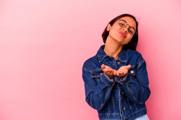 ピンクの壁に孤立した若い混血の女性は、唇を折り、手のひらを持ってエアキスを送信します。