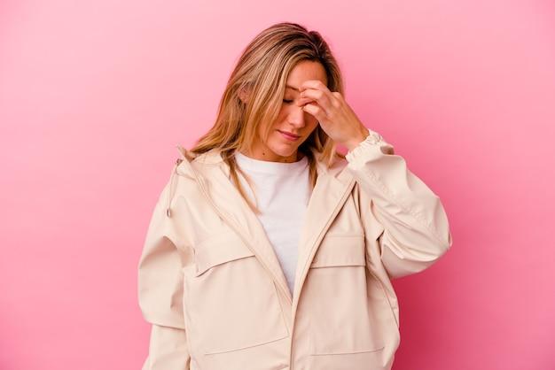 젊은 혼합 된 인종 여자 머리 아파도 데 분홍색 벽에 고립 된 얼굴 앞을 만지고.