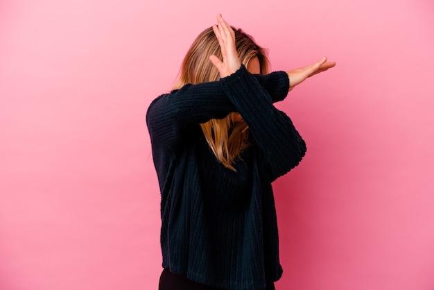 두 팔을 유지하는 분홍색 벽에 고립 된 젊은 혼혈 여자 넘어, 거부 개념.