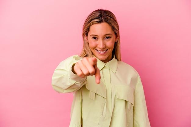 손가락으로 앞을 가리키는 분홍색 벽에 고립 된 젊은 혼합 된 인종 여자.