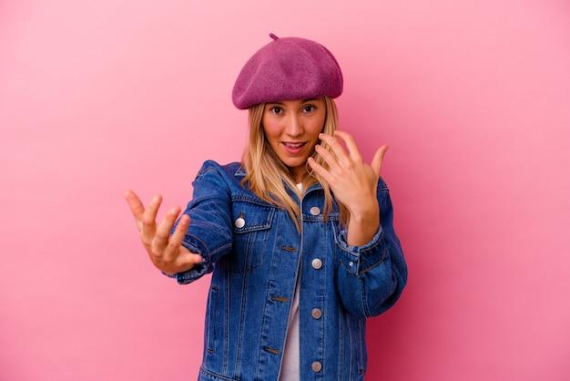 젊은 혼혈 여자 초대 가까이 와서 당신 손가락으로 가리키는 분홍색 벽에 고립.