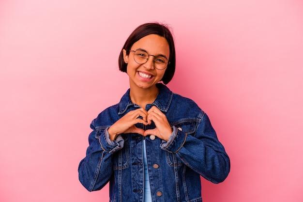 웃 고 손으로 심장 모양을 보여주는 분홍색 벽에 고립 된 젊은 혼합 된 인종 여자.