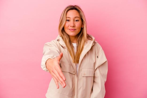 인사말 제스처에 카메라에 손을 스트레칭 분홍색 벽에 고립 된 젊은 혼합 된 인종 여자.