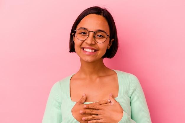 Молодая женщина смешанной расы изолирована на розовой стене, принимая присягу, положив руку на грудь.
