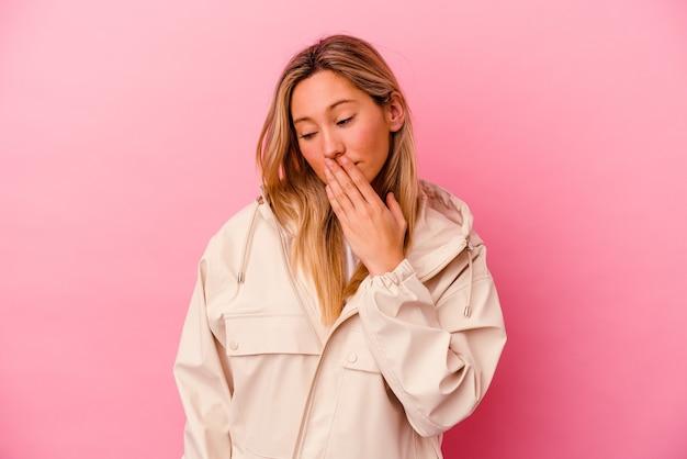 Молодая женщина смешанной расы изолирована на розовой стене, зевая, показывая усталый жест, закрывающий рот рукой.