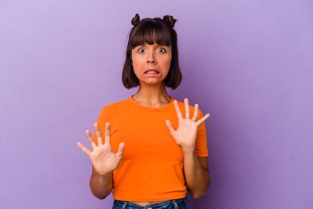 Молодая женщина смешанной расы, изолированная на фиолетовом фоне, шокирована из-за неминуемой опасности