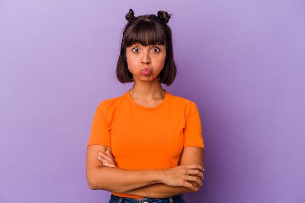 보라색 배경에 고립된 젊은 혼혈 여성은 뺨을 불고 피곤한 표정을 짓고 있습니다. 표정 개념입니다.