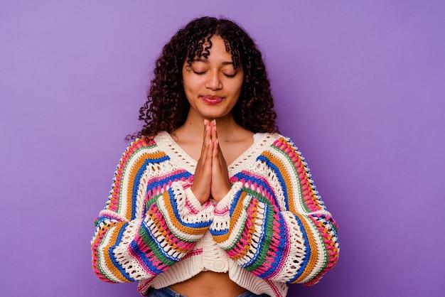口の近くで祈って手をつないで紫色の背景に分離された若い混血の女性は、自信を持っています。