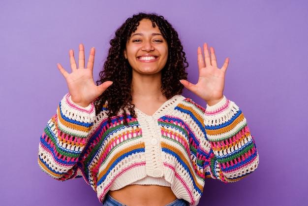 Молодая женщина смешанной расы, изолированные на фиолетовом фоне, показывая номер десять руками.