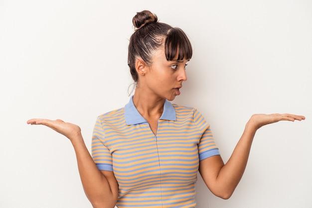 흰색 배경에 격리된 젊은 혼혈 여성은 복사 공간을 잡기 위해 혼란스럽고 의심스러운 어깨를 으쓱하고 있습니다.