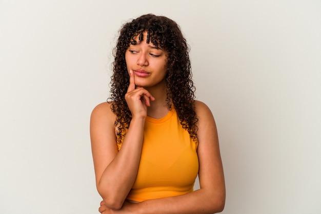 白い背景に若い混血の女性が考え、戦略を立て、ビジネスのやり方を考えた。