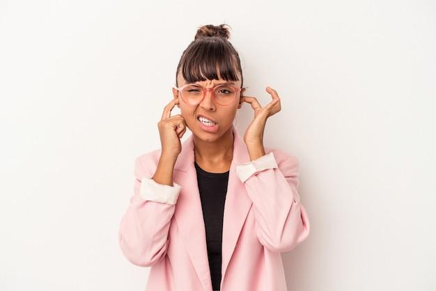 指で耳を覆う白い背景で隔離され、大声で周囲によってストレスと絶望的な若い混血の女性。