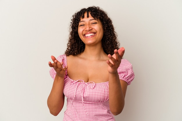 白い背景で隔離の若い混血の女性は、カメラに抱擁を与える自信を持っています。