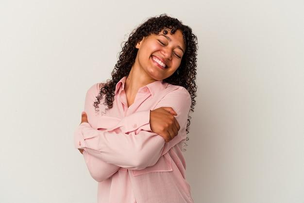 白い背景の抱擁に分離された若い混血の女性は、のんびりと幸せに笑っています。