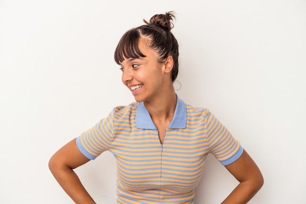 白い背景で隔離の若い混血の女性は幸せに笑い、胃に手を保つことを楽しんでいます。