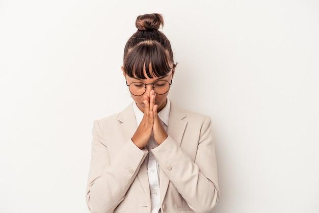祈り、献身を示し、神のインスピレーションを探している宗教的な人を祈って、白い背景で隔離の若い混血の女性。