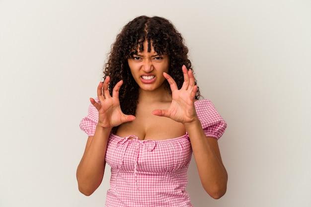 猫を模倣した爪、攻撃的なジェスチャーを示す白い背景で隔離の若い混血の女性。