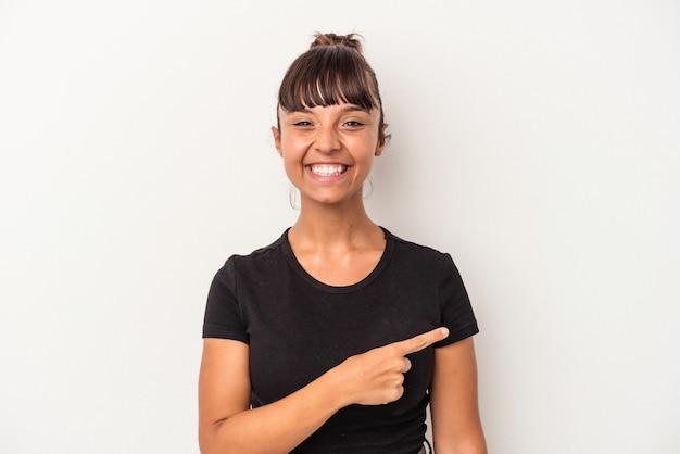 笑顔と脇を指して、空白のスペースで何かを示して、白い背景で隔離の若い混血の女性。