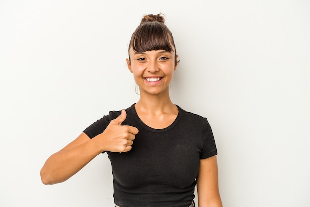 笑顔と親指を上げる白い背景で隔離の若い混血の女性