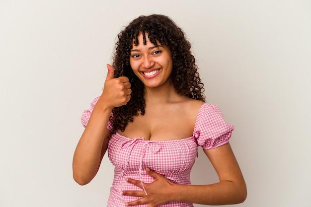 흰색 배경에 격리된 젊은 혼혈 여성은 배를 만지고 부드럽게 미소 짓고 식사와 만족 개념을 합니다.