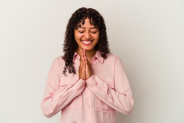 口の近くで祈って手をつないで白い壁に隔離された若い混血の女性は、自信を持っています。