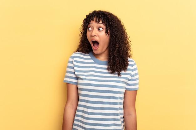 彼女が見た何かのためにショックを受けている黄色の背景に孤立した若い混血の女性。