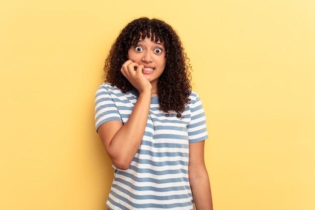 노란색 배경에 격리된 젊은 혼혈 여성은 손톱을 물어뜯고 긴장하고 매우 불안해합니다.
