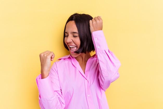 Молодая женщина смешанной расы, изолированные на желтом фоне, празднует особый день, прыгает и поднимает руки с энергией.