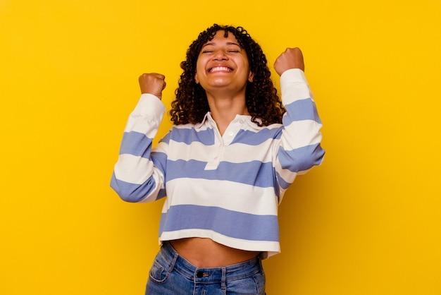 승리, 열정과 열정, 행복 식을 축하하는 노란색 배경에 고립 된 젊은 혼합 된 인종 여자.