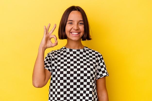 Молодая женщина смешанной расы, изолированные на желтом фоне, веселая и уверенная, показывая одобренный жест.