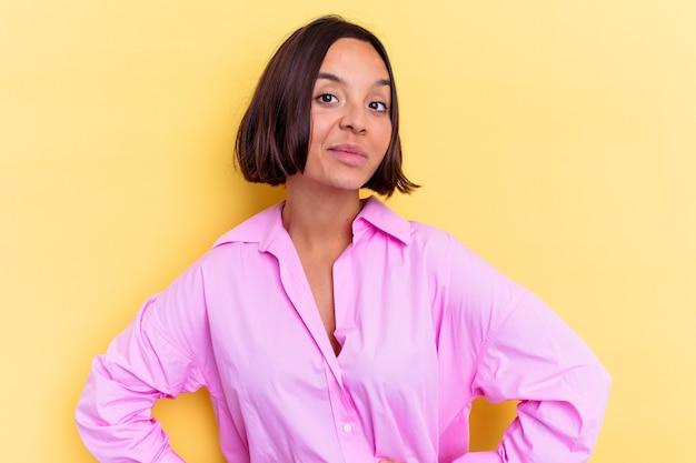Молодая женщина смешанной расы, изолированные на желтом фоне, уверенно держа руки на бедрах.